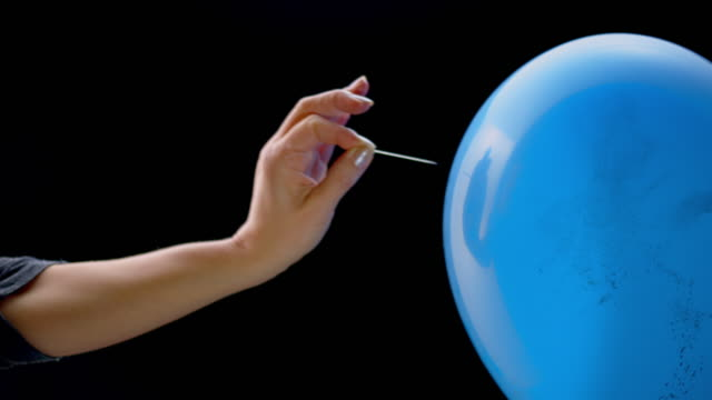 SLO MO LD Female hand popping a balloon filled with confetti with a pin