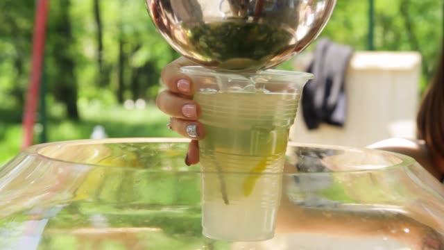 vídeos de stock e filmes b-roll de female hand pouring fresh lemonade into a glass - limonada tradicional