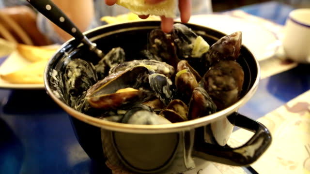 Female hand pours a lemon juice to mussels in a sauce of gorgonzola cheese. Woman eating tasty mussels in open air seafood restaurant. video
