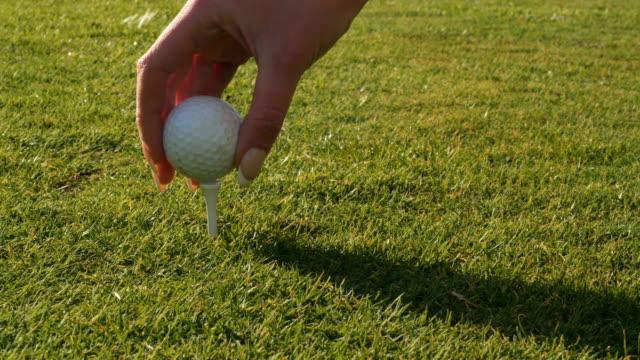 t シャツにゴルフボールを置く女性の手 - ゴルフ点の映像素材/bロール
