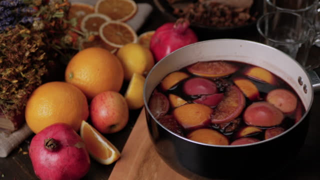 Female hand putting a saucepan of hot mulled wine on cutting board. Fresh lemons, oranges, pomegranate and dried herbs in background. Steam from wine soar over the saucepan