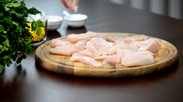 female hand salting chicken fillet - filetto video stock e b–roll