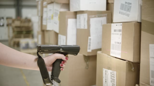 Female hand scanning packages with a handheld scanner video