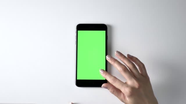 weibliche hand scrollen auf großen schwarzen smartphone. green-screen, chromakey konzept, top shot 60 fps - schriftrolle stock-videos und b-roll-filmmaterial