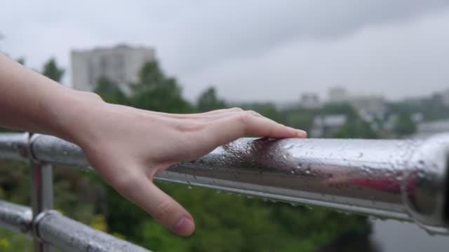 Female hand shakes off raindrops from metal handrail of protective guarding. video