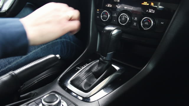 Female hand shifts gears. Automatic transmission, automatic gear shift, is moved from P to D. Park to Drive Female hand shifts gears. Automatic transmission, automatic gear shift, is moved from P to D. Park to Drive. stick plant part stock videos & royalty-free footage