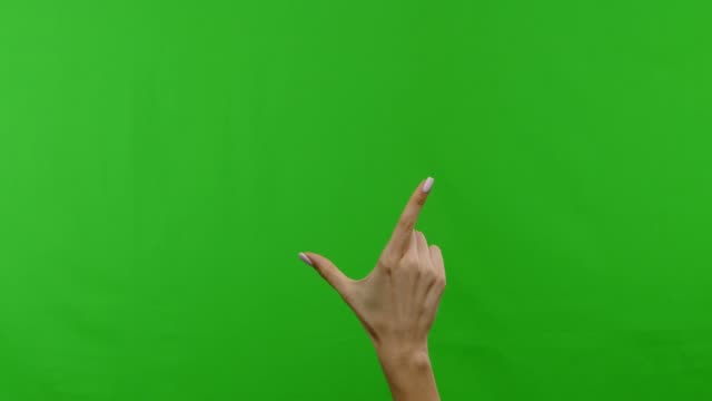 Female hand showing multitouch gestures on green touchscreen Touchscreen gestures. Female hand showing multitouch gestures on green chroma key background pinching stock videos & royalty-free footage