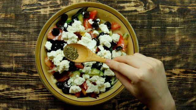 Female hand sprinkle seasoning from wooden spoon on vegetarian low calorie Greek salad. top view Close-up video