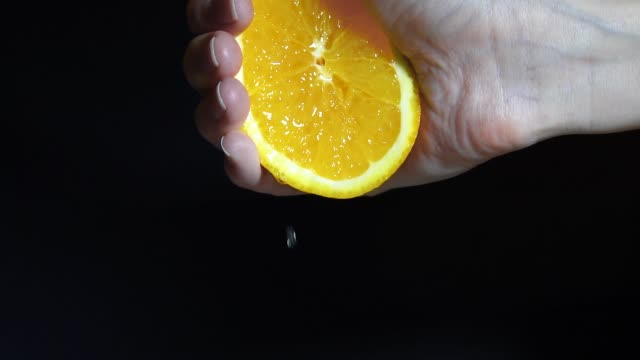 female hand squeezing fresh orange juice. Hand squfemale hand squeezing fresh orange juice. Hand squeezing an orange. Slow motioneezing an orange. Slow motion