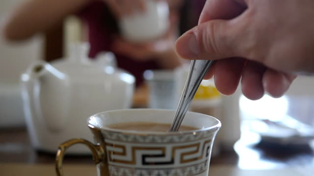 Female hand stirring sugar or milk in a cup of hot coffee or tea. Slow motion