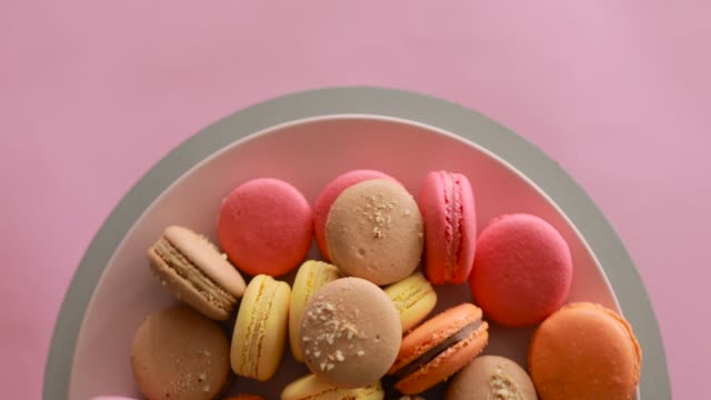 Female hand take one macaroon from rotating colorful cakes set video