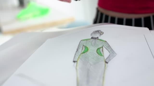 vídeos de stock e filmes b-roll de female hand takes glasses, lying near image of a sketch of clothes in atelier - trabalho de design