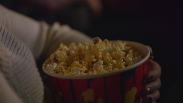 vídeos de stock, filmes e b-roll de feminino mão tirando pipoca de recipiente de papel. comer pipocas no cinema - balde pipoca