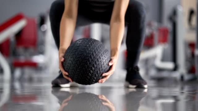vídeos de stock e filmes b-roll de slo mo female hand throwing fitness ball to the ground - agachar se