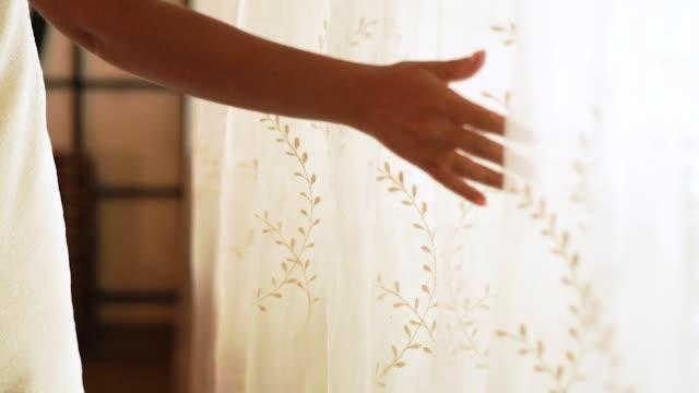 kvinnliga hand vidröra vita gardiner i mysigt sovrum. ung kvinna insvept i bad hand duk i sovrummet interiör. hus design och inrednings koncept - röra vid bildbanksvideor och videomaterial från bakom kulisserna