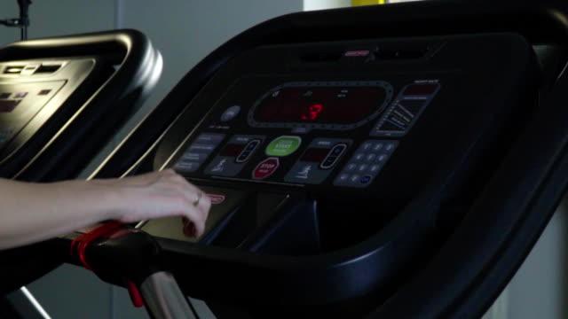 Weibliche Hand drehen auf einem Laufband auf dem Bedienfeld – Video