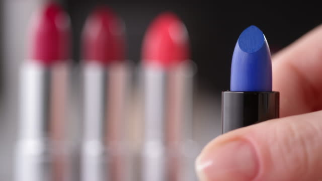 Female Hand Twisting Blue Lipstick Up on Makeup Desk