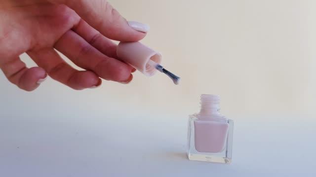 en kvinnlig hand med en vacker manikyr öppnar en beige pastell i färgen på nagellack. kopiera utrymme - nagellack bildbanksvideor och videomaterial från bakom kulisserna