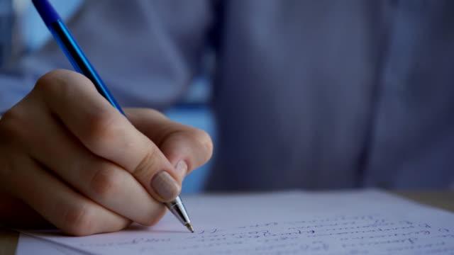 vídeos de stock e filmes b-roll de female hand with clock quickly writes blue pen on paper text - mensagem