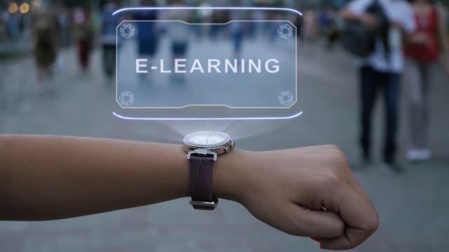vidéos et rushes de main femelle avec l'hologramme e-learning - étudiant(e)