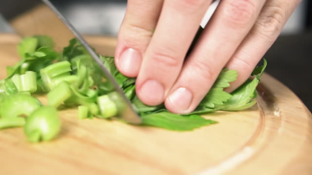 female hand with knife cuts stalk of celery, slow motion. concept of healthy food. - disintossicazione video stock e b–roll