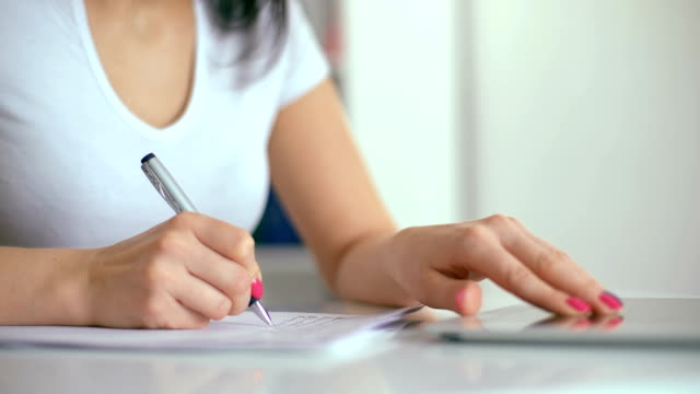 Female hand with pen writing in notebook video