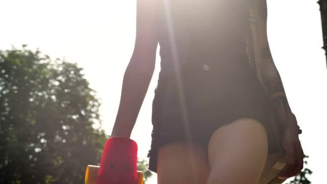 female hand with tattoo holding skateboard and backpack and legs in shorts going forward near university, lens flare - pantaloncini video stock e b–roll