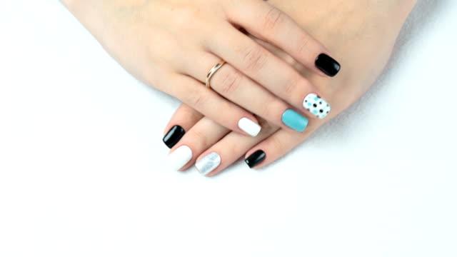 weibliche hand mit trendiger maniküre. nageldesign auf weißem hintergrund nahaufnahme - maniküre stock-videos und b-roll-filmmaterial