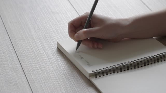 Female hand writes a note in a notebook. A letter to a friend. Poetry in the reflected light. Fast writing. video