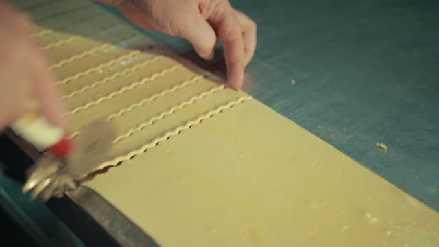 Female hands are cutting elastic flat dough into thin equal pieces.
