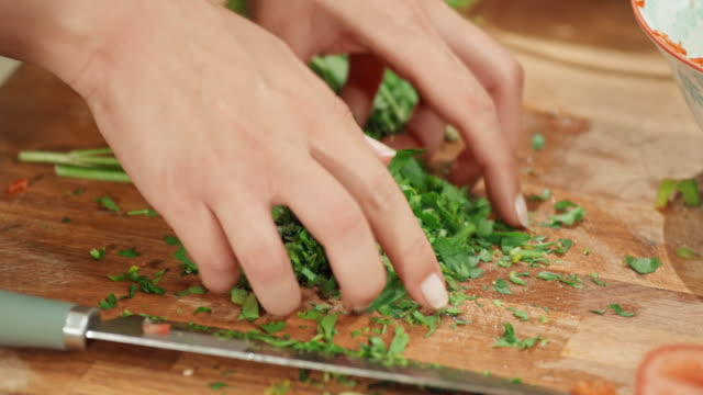 Female hands chopping fresh herbs on a wooden board and putting it on a salad video