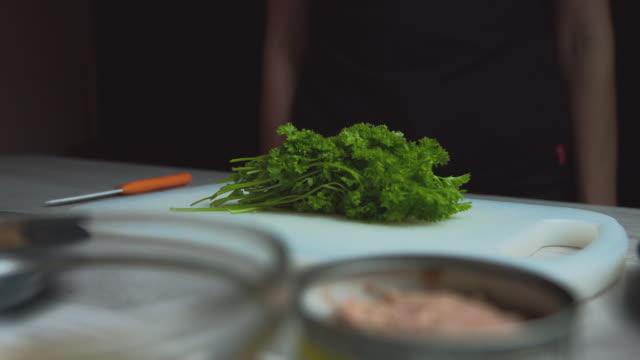 female hands close up cut parsley, prepare a vegetarian salad