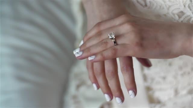 Manos femeninas de cerca con enfoque de rack de diamante anillo de oro plata. Ropa de mujer boda compromiso anillo en dedo pulido uñas encaje vestido de preocupación antes de la ceremonia. Vida de la riqueza ricos glamour Cenicienta - vídeo
