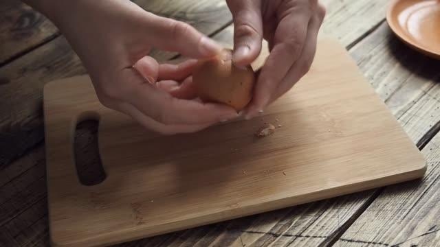 vídeos de stock e filmes b-roll de female hands close-up clean boiled chicken egg. home kitchen wooden table - castanho