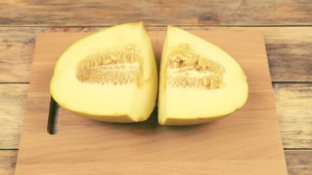 Female hands cut a melon in half with a knife on a cutting board.
