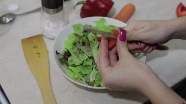 vídeos de stock e filmes b-roll de female hands cut a sweet red bell pepper to a salad - red bell pepper isolated