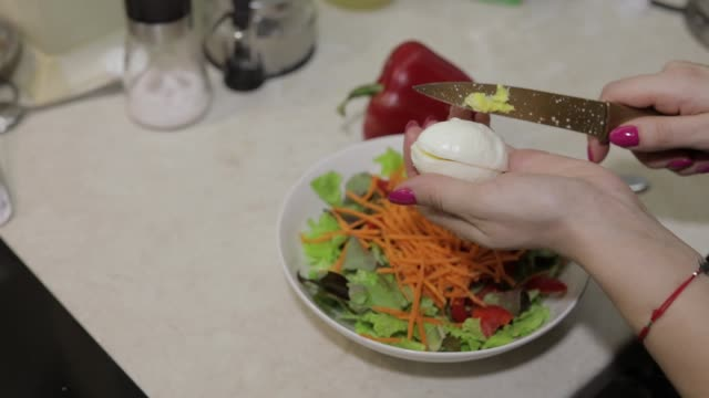 vídeos de stock e filmes b-roll de female hands cut an egg to a salad with red bell pepper and lettuce salad - red bell pepper isolated