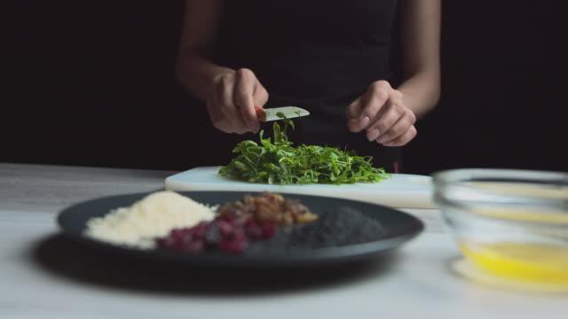 female hands cut green salad, seasoning on the table, vegetarian food, summer salad