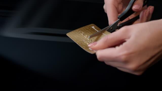 Female hands cutting credit card with scissors. Debit card account closing Female hands cutting credit card with scissors. Debit card account closing. Scissors cutting bank card. Stop to pay money. Financial crisis concept. Destroy credit card. Stop spending on shopping cutting stock videos & royalty-free footage