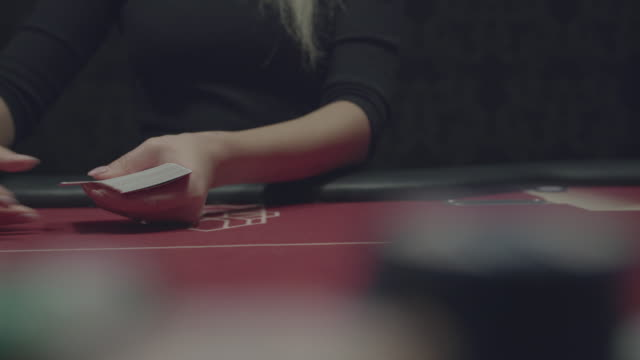 Female hands deal cards during a play of poker at the camera video