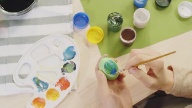 female hands decorating green easter egg - four seasons filmów i materiałów b-roll