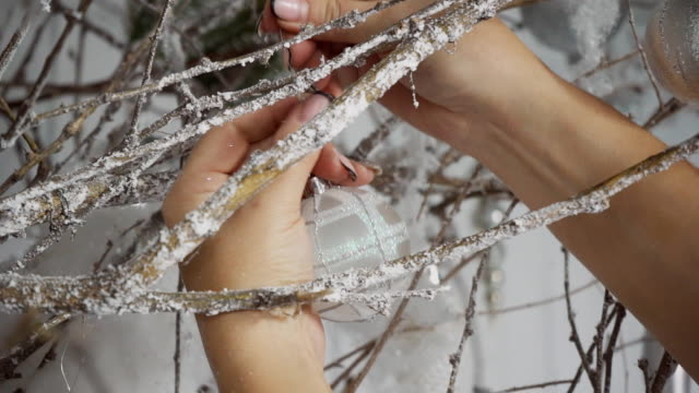 Female hands fix gray ball on branches covered with artificial frost video