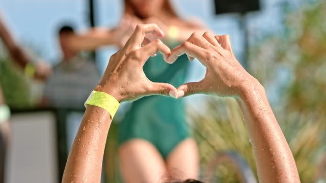 SLO MO Female hands forming a heart at a party outside Slow motion medium handheld shot of a woman forming a heart shape with her hands at a party outside on a sunny day. Shot in Slovenia. pool party stock videos & royalty-free footage