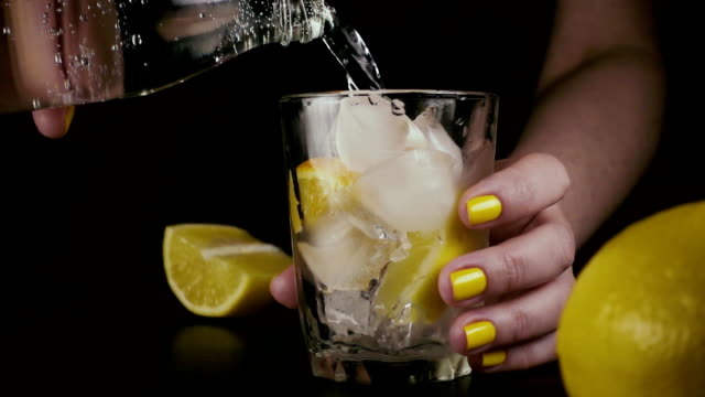 Female hands from a bottle pour water into a glass. Slow mo Female hands from a glass bottle pour soda water into a glass with ice and lemon. Slow mo carbonated stock videos & royalty-free footage