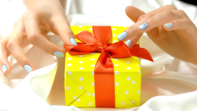 female hands gently touching gift box. - nastro per capelli video stock e b–roll