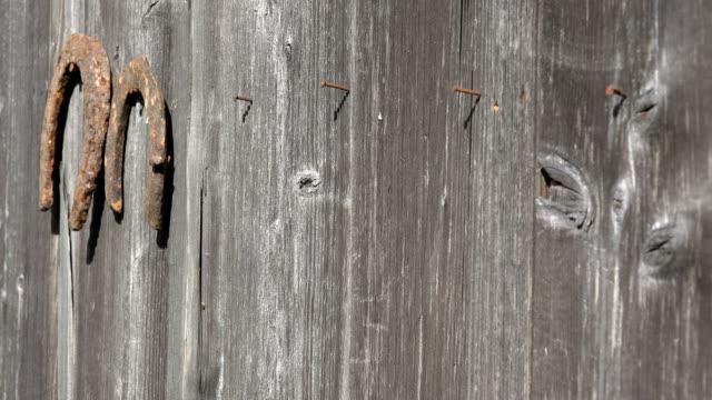 女性の手は、木製の田舎の家の壁から錆び蹄鉄をハングアップします。クローズ アップ。4k - 吊るす点の映像素材/bロール