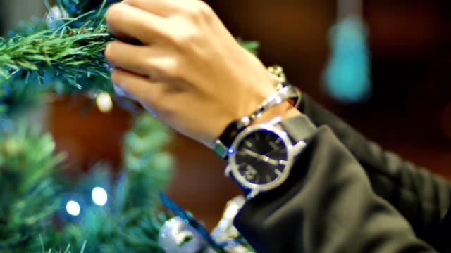 female hands hanging balls on the christmas tree. winter holidays christmas and new year decoration. blinking garland. christmas tree lights twinkling - jodła filmów i materiałów b-roll