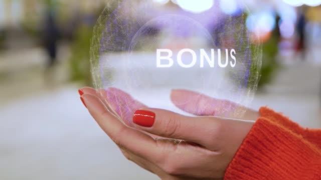 female hands holding a conceptual hologram bonus - bonus video stock e b–roll