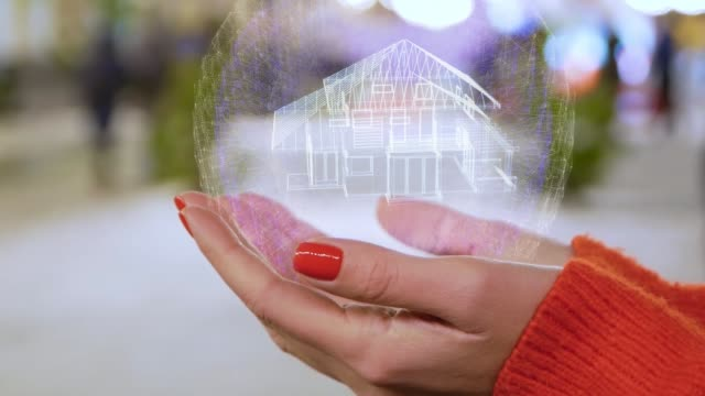Female hands holding a conceptual hologram with house