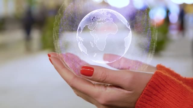 Female hands holding a conceptual hologram with the planet Earth
